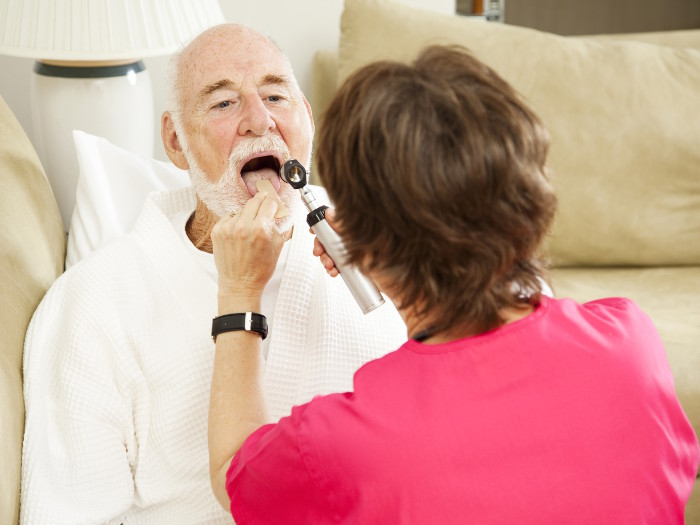 Home health care nurse looks in a patient's throat.